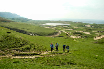 Picture of walkers walking up some dunes, sea in the background