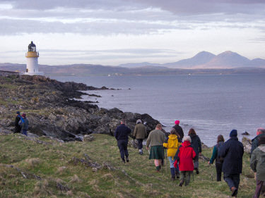 Picture of walkers on a shore approaching a lighthouse
