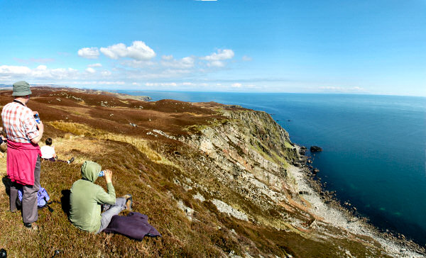 Picture of a panoramic view of walkers sitting on a cliff overlooking the sea