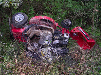 Picture of a partly burned lawnmower lying on the side in a ditch