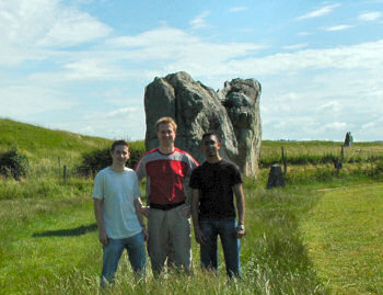 Picture of three people in front of some standing stones