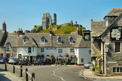 Picture of an old English village with the ruins of a castle in the background
