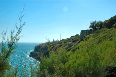 Picture of cliffs on a coastline in brilliant sunshine, a lighthouse in the distance