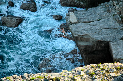 Picture of a young man jumping off a cliff into the sea