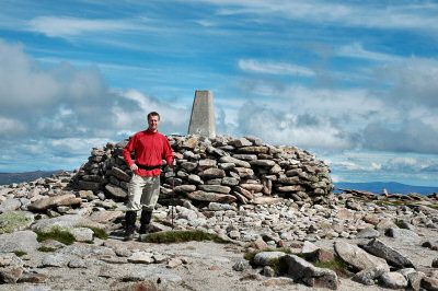 Picture of a walker in front of the summit cairn and trig point on Ben Macdui