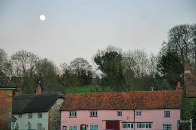 Picture of the moon over a pink row of cottages