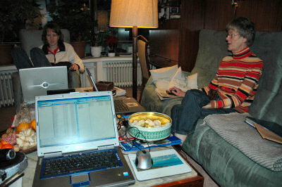 Picture of three laptops on a large coffee table with two woman sitting at them