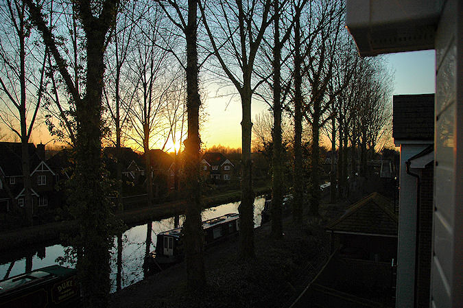Picture of a sunset over a canal lined with trees, sun still visible low in the sky
