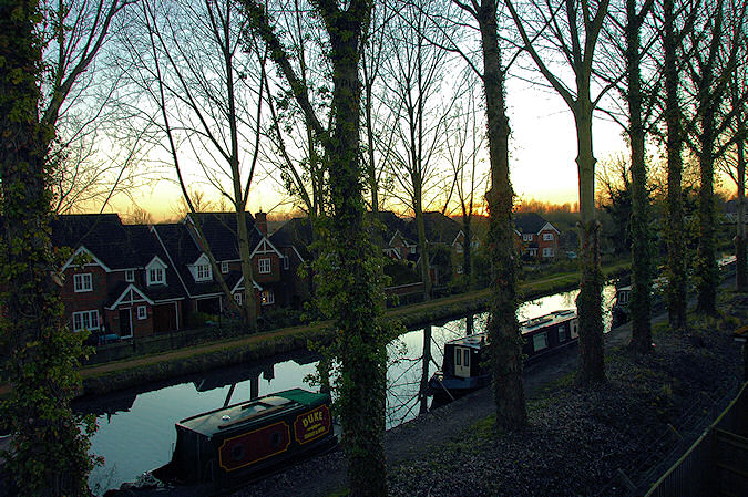 Picture of a sunset over a canal lined with trees, the sun has just disappeared