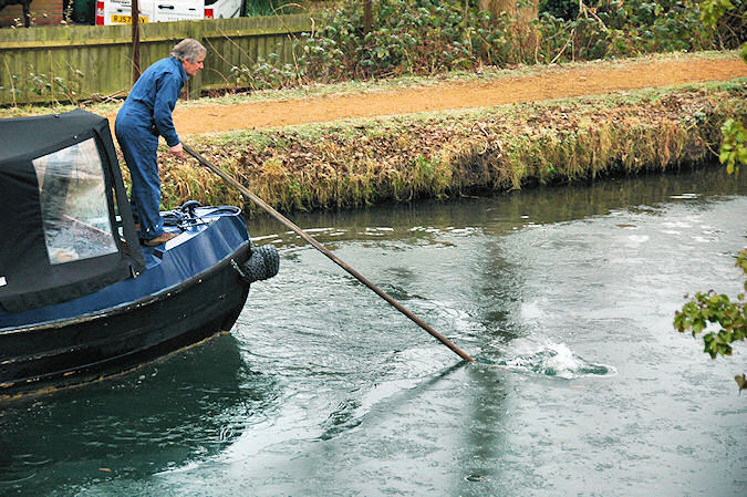 Picture of a man standing on the bow of a canal boat breaking ice on the water with a pole