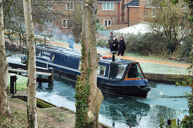 Picture of a canal boat leaving a lock during the winter