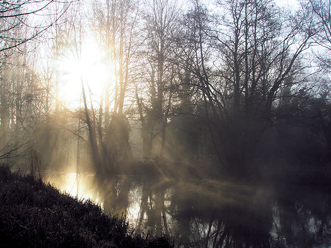 Picture of mist rising over a canal, the sun shining through it