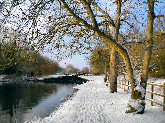 Picture of view along a canal towards a canal lock in the snow
