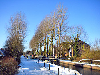 Picture of a canal lock with an apartment building in bright winter sunshine