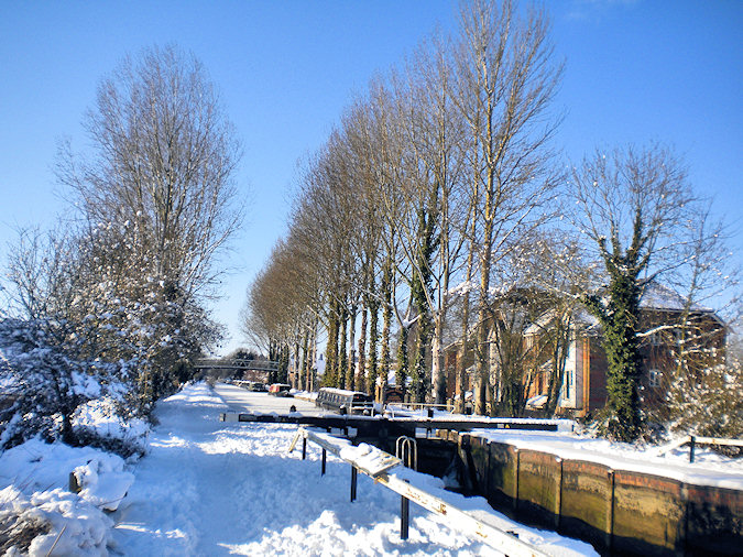 Picture of a canal lock and tree lined canal path after heavy snowfall