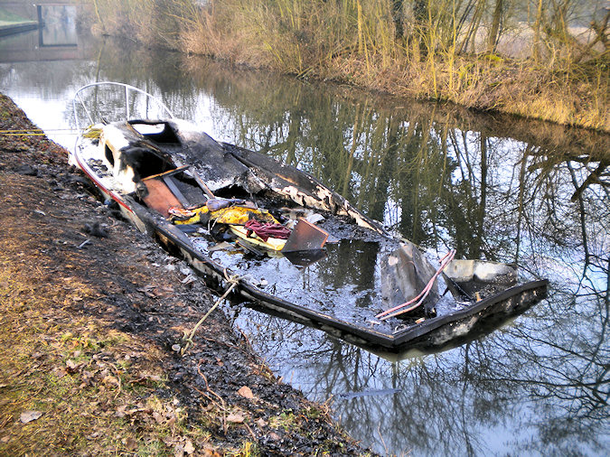 Picture of a burned out small sports boat on a canal