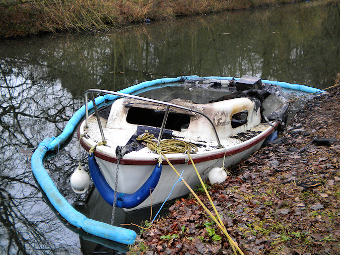 Picture of a burned out small sports boat surrounded by a swimming barrier