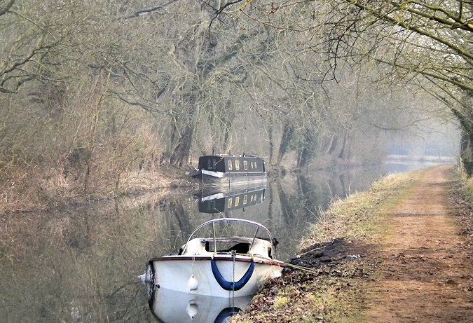 Picture of a burned out small sports boat, another canal boat in the background